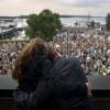 Two girls embrace on a balcony overlooki