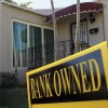 A bank owned sign is seen in front of a foreclosed home on December 7, 2010 in Miami, Florida.