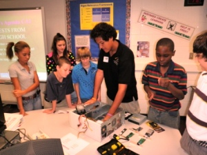 Dunbar technology student demonstrates hardware to middle school students.
