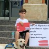 Henry Miles Frost and his service dog, Denzel, protest outside a downtown Tampa building during the Republican National Convention. Since he posted the photo to Facebook, he's found global support in his effort to enroll in his South Tampa neighborhood school.