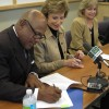 "Hillsborough Community College president Ken Atwater signs a ""reverse transfer"" agreement Monday as University of South Florida president Judy Genshaft looks on. The agreement allows students who transfer to the University of South Florida to earn credits toward an associate's degree from one of four Tampa Bay colleges."
