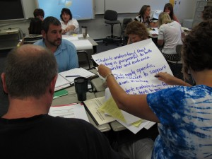 Venice High School English teachers, from left, Larry Burke, Kathleen Jones and LaRay Biziawski write a learning goal at a recent Common Core training. Venice High School assistant principal Joshua Leinweber, in the blue shirt, joined them.