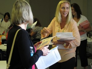 Cynthia Crim hands out Common Core materials to teachers following a math training session.
