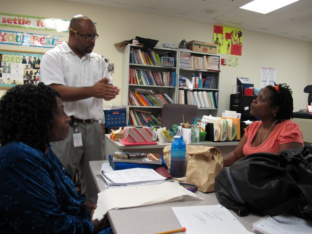 Uzelea Evans, right, and TKTK TKTK, left, talk with GED teacher Travis McGinnis at Metropolitan Ministries. The GED is changing in January, and McGinnis said his students have been planning since September whether to take the old test or the new GED.