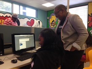 Felecia Hatcher helps a student write HTML code.