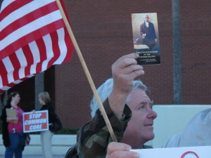 A man holds up a copy of the Constitution to oppose Common Core before a State Board of Education meeting in Orlando.