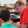 Monroe Middle School science teacher Andrea Groves works with a student. Many science classes will add more reading and writing assignments as Florida finishes the switch to new K-12 math and language arts standards this fall.