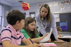 Laurie Langford, a second grade teacher at West Defuniak Elementary, helps two students look for evidence in a reading passage about public sector jobs.