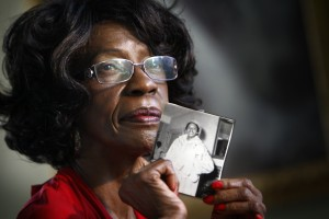 Mamie Pinder, holds a photograph of herself as a young teaching student. Pinder, a retired Miami-Dade school teacher, began teaching in 1963, the year the school district began merging black and white students bodies and faculty.
