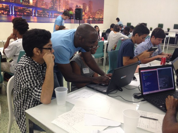 CodeNow's Kareem Grant works with students during a June coding camp in Miami. Grant likes that coding requires disciplined thinking.