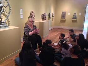 A volunteer docent at the St. Petersburg Museum of Fine Arts explains a 19th century Indian statue of the Hindu God, Shiva as the King of Dance.