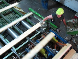 A worker mans a machine as lumber headed to the stacker at the Emerald Forest Products mill.