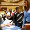 Job seekers wait in line to speak with potential employers.