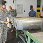 Lt. Gen. James Pillsbury removes the rear casing plate of a bomb at the McAlester Army Ammunition Plant.