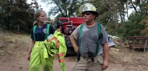 Christie Smith, a full-time nurse and volunteer firefighter with the Cedar County Fire Department, and David Thompson, safety officer with the Slaughterville Fire Department, cool down after extinguishing a hotspot that flared east of Noble, Okla.