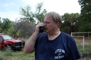 "Allen Schneider, chief of the Little Axe Fire Department, on the radio during a ""mutual aid"" call near Noble, Okla. Firefighters from Little Axe teamed up with volunteer firefighters from Cedar Country and Slaughterville to extinguish hotspots after a devastating firestorm in early August."