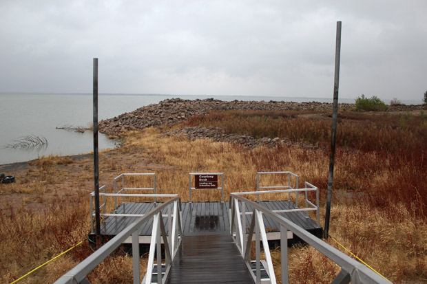 Drought-related withdrawals from Canton Lake has left boat docks floating on dirt and grass.
