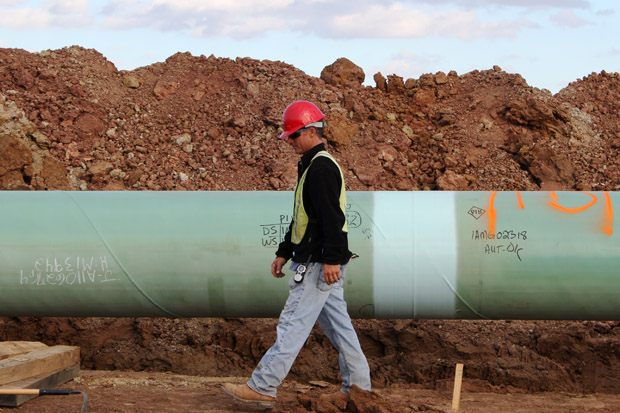 A worker inspects a segment of the Keystone Pipeline before it's lowered into a trench near Stroud, Okla.