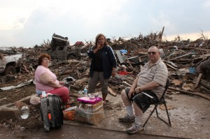 Stella and Jack Howard (left and right) with their daughter, Dawnelaina (center), sit with the remains of their Moore home. The Howards built this house after their last one was destroyed by the May 3, 1999, twister.