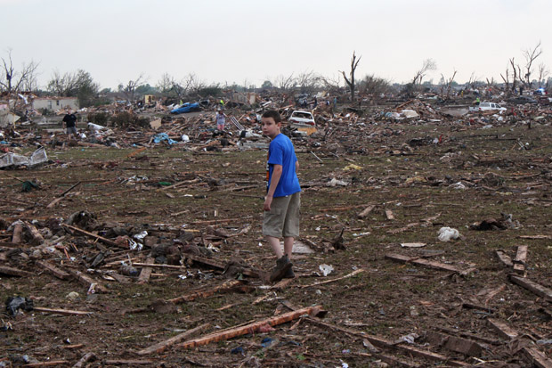 Eleven-year-old Gavin Hawkins stand near the rubble of the Plaza Tower Elementary School. His dad, Joel, rushed to the school to pick up his son before the storm hit.