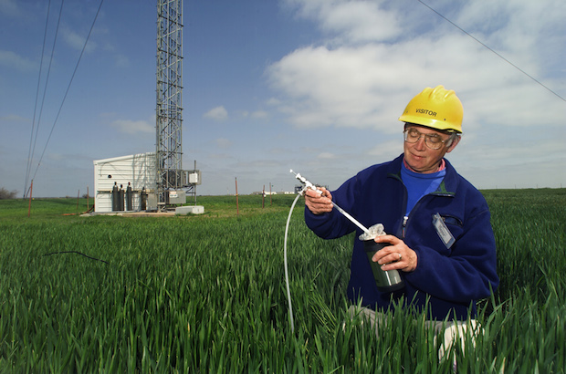 A scientist at the Southern Great Plains research facility in Lamont, Okla., transfers air samples to a flask for transport back to a lab. The new methane study used similar air sample data collected by the U.S. Department of Energy and NOAA during thousands of aircraft flights and from stationary towers throughout the country.