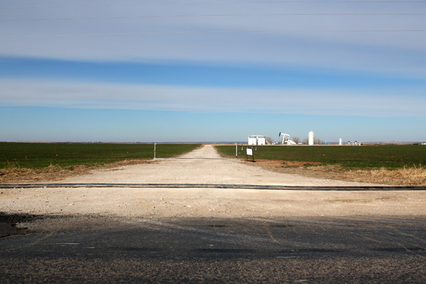 A water line for hydraulic fracturing traverses an oil and gas access road in Woods County.