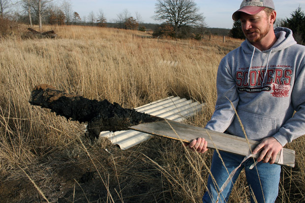 Tyler Lane pulls up a wooden marker covered with oily sludge in the land behind his Bristow home. Lane uses stakes and rope to keep his two children out of the oiliest, most dangerous parts of his land, which sits atop the abandoned Wilcox Refinery, Oklahoma's newest Superfund site.