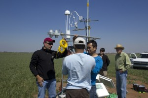 University of Oklahoma meteorology professor Jeffrey Basara installs equipment in a wheat field (left) with the help of postdoc researcher Pradeep Wagle and Ph.D. student Yuting Zhou, as other Grazinglands scientists look on.