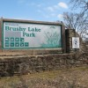 The word 'state' has been removed from Brushy Lake Park's entrance sign. The park, near Sallisaw, Okla., was transferred to the city's control in 2011.