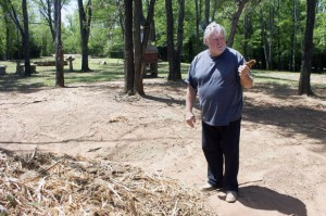 Homeowner Larry Huff holds a shard of Eastern Red Cedar, the handiwork of an Oklahoma County program that clears the flammable tree from private property.