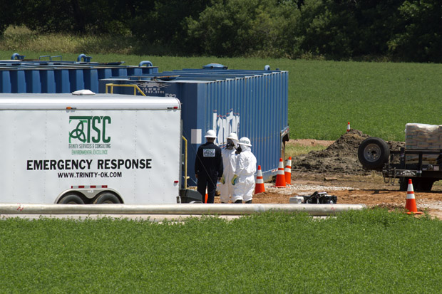 Crews work to contain and clean up 20,000 gallons of hydrochloric acid that spilled near a hydraulic fracturing site near Hennessey, Okla.