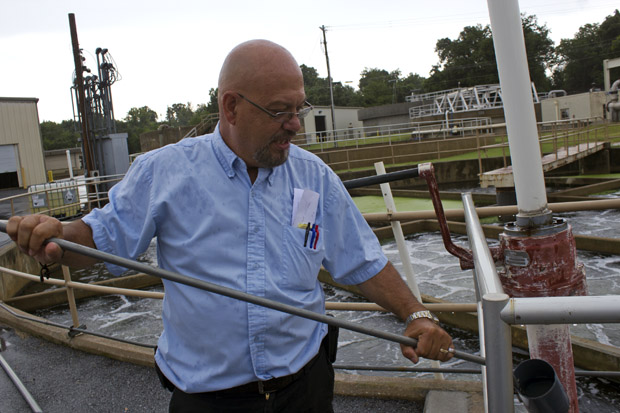 Tom Myers, superintendent of the new wastewater treatment plant in Siloam Springs, Ark., holds a sample of treated water that will be discharged into Oklahoma's Flint Creek.