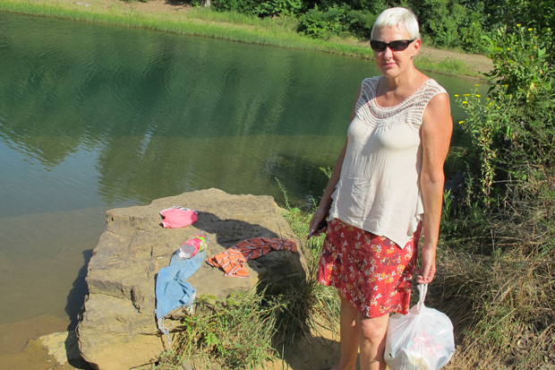 Debbie Doss picks up garbage and loose clothing left behind by careless tourists along Lee Creek.