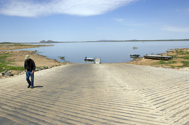 A fisherman walks up a dry boat dock at Tom Steed Reservoir. The lake is only 24 percent full and supplies water for Altus and other cities nearby.