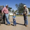 Monte Tucker, left, stands with his son and dad on the family's farm near Sweetwater, Okla.