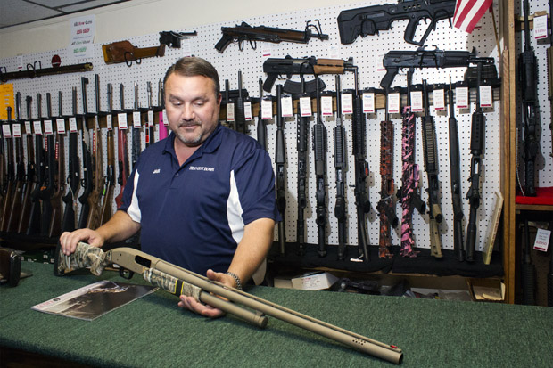 Jack Barrett, owner of the BDC Gun Room in Shawnee, Okla., shows off a new shotgun model popular with hunters.