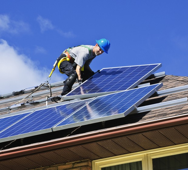 A worker installs a rooftop solar panel.