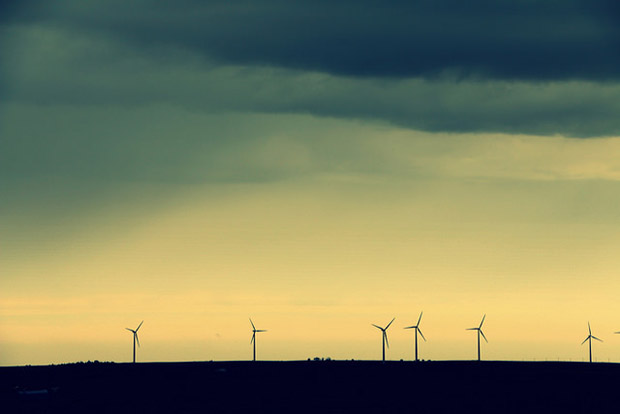 A line of wind turbines dot a stormy horizon in Oklahoma.