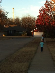 Stillwater resident Tammy Mix's sons play on the sidewalk as a drilling rig peeks above the tree line behind her Stillwater home in 2014.