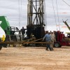 Oil-field workers lining up a section of pipe at a disposal well in Grant County, Okla.