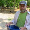 Dustin Green, owner of 10 Acre Woods farm near Norman, feeds a few of his 400 or so chickens.