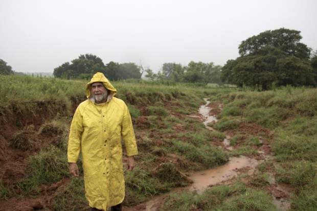 Oklahoma Conservation Commission Watershed Technitian Dennis Boney inspects damage to the Wildhorse 80 dam's spillway in Garvin County in July 2015.