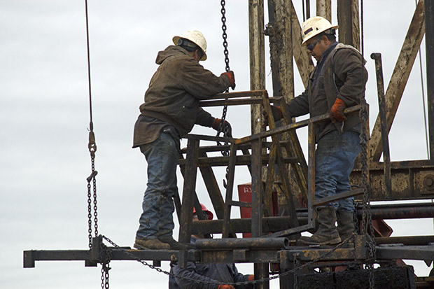 Workers uncap a well in the western Oklahoma oil field in 2014.