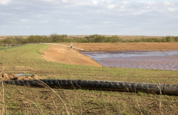 A pipe deposits sludge into a 17-acre pit near Waurika Lake, where it will be left to dry.