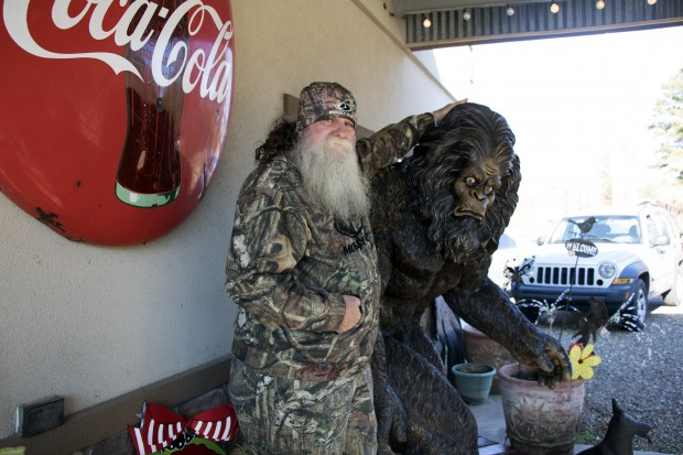 Charles Benton, who claims to have seen Bigfoot, stands with a statue of the creature in front of Janet's Treasure Chest in Honobia, Okla.