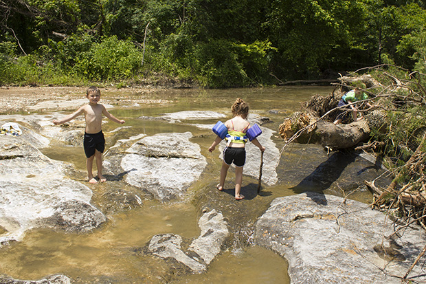 Children play in a small tributary of the Illinois River near Tahlequah, Okla., in May 2015.