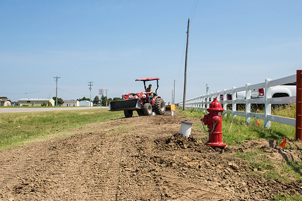 A worker with the Citizen Potawatomie Nation smooths out dirt and gravel poured atop a disputed water pipe laid alongside U.S. Highway 177.