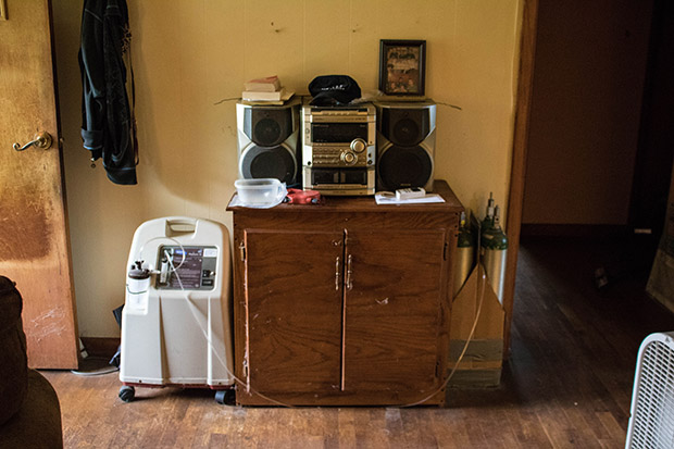 An oxygen concentrator and bottles of oxygen in the entryway of Susan Holmes' home near Bokoshe, Oklahoma.