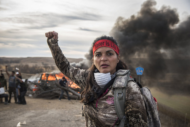 A field medic raises her fist as protestors stand near a fire blocking a road along the Dakota Access Pipeline Route near the Standing Rock Sioux Reservation in North Dakota.