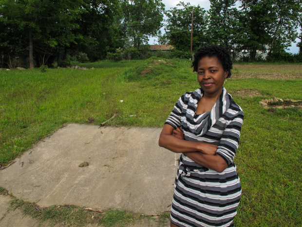 Sherry Laskey stands near land she bought in a north Tulsa neighborhood. Laskey is hoping to turn the empty lot into a profitable community garden that provides healthy food for the area.